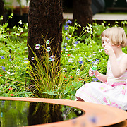 LONDON, UK - 21 May 2012: a 5 year old girl enjoys playtime at the World Vision Garden during the RHS Chelsea Flower Show 2012.