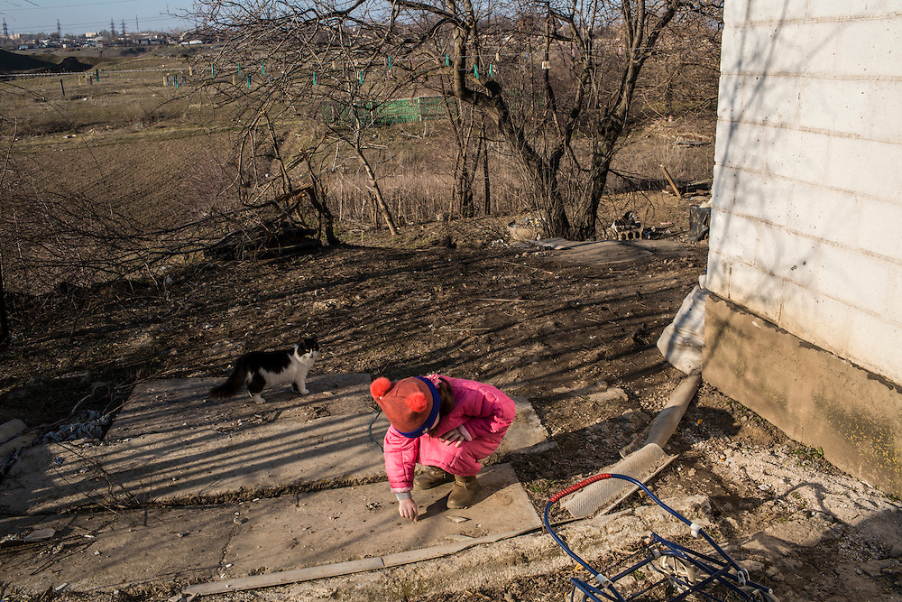 Ira searches for pieces of shrapnel from a shell that on January 19 landed in her yard on Monday, March 9, 2015 in Sartana, Ukraine. Photo by Brendan Hoffman, Freelance