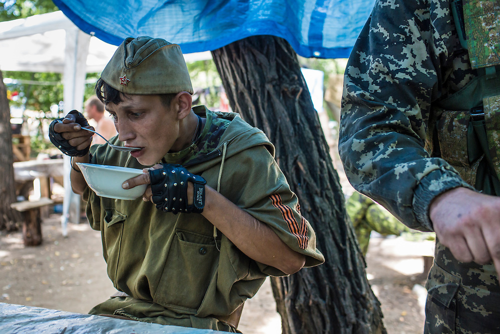 A pro-Russia rebel eats borscht at a camp by a checkpoint on the outskirts of the city on Monday, July 28, 2014 in Horlivka, Ukraine.