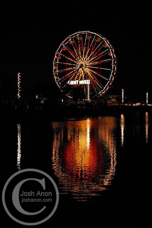 A ferris wheel reflects into the water at a 4th of July celebration in San Rafael, California.
