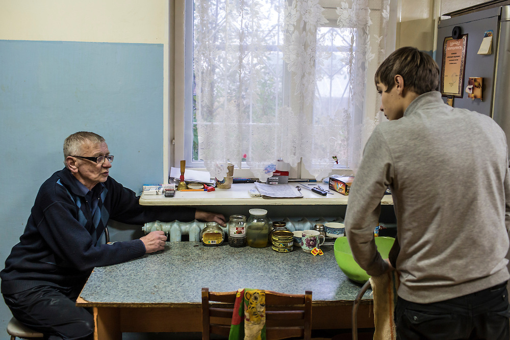 YEKATERINBURG, RUSSIA - OCTOBER 16: Alexandr Fedorovich (L), the live-in supervisor at a facility for at-risk teenage boys run by City Without Drugs, advises a boy tasked with cooking dinner on October 16, 2013 in Yekaterinburg, Russia. Nine boys, many of whom were either experimenting with drugs or had dropped out of school, live at the group home, where school attendance and homework are mandatory. City Without Drugs is a well-known narcotics treatment program in Russia founded by Yevgeny Roizman, who was elected mayor of Yekaterinburg in September 2013. (Photo by Brendan Hoffman/Getty Images) *** Local Caption *** Alexandr Fedorovich
