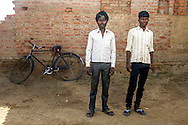 Ram Jatan and Mahinder Vanvasi stand for a portrait next to their bike on April 22, 2016 in Varanasi, Uttar Pradesh, India. On the night of April 13, Ram Jatan and Mahinder Vanvasi escaped from a brick kiln in the state of Uttar Pradesh, India. They rode 12 miles on a bicycle to their home village to find help. The men and their families had been forced into bonded labor, unable to earn enough money to pay back an advance the kiln owner had given them. Their families were rescued on June 8.<br />