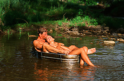 couple in a metal bucket in a stream