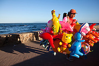 Philippines Balloon Vendor along Rizal Boulevard in Dumaguete.  The Boulevard is immediately visible when coming into Dumaguete port via any ferryboat.  From the white lamp posts lining up the stretch off sea wall to the stately palms swaying in the breeze, The Boulevard is a favorite landmark for both residents, kids and visitors of all ages.