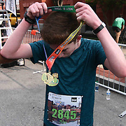 Fifth-teen year old Mike Ward (2845) of Ephrata, PA., puts on his medal after finishing the 13th Annual Discover Bank Delaware Marathon Sunday, May 8, 2016, at Tubman Garrett Riverfront Park, in Wilmington Delaware.