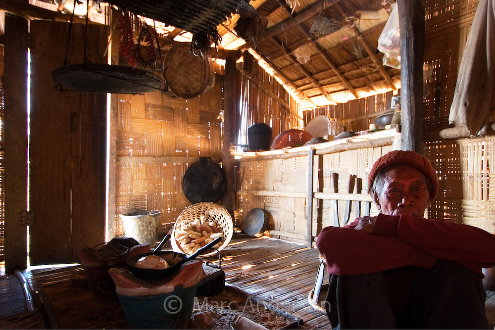 Old man sitting in a traditional bamboo hut near Tha Ton, Thailand