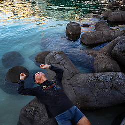 Ninety-one-year-old Fumiyasu Yamakawa stretches his back on a rock as he does morning exercises in Naha, Okinawa.