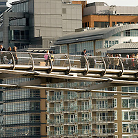 UK. London. Bankside on London's Southbank. People walk across the Millenium Bridge.