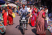 An Indian man is riding motorcycle in a street market in Mumbai, India, on  January 28, 2015.<br />