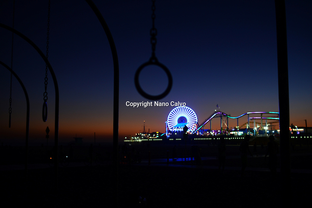 Exercise rings and Pacific Park in Santa Monica at night.