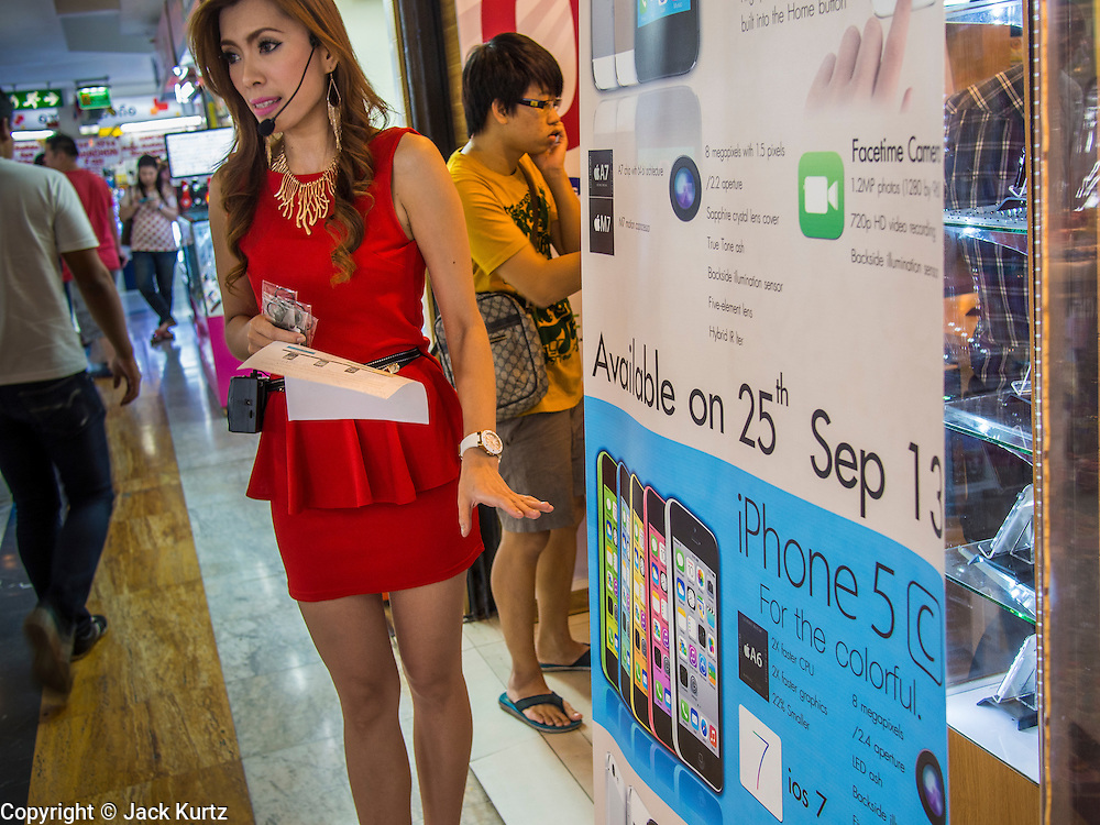 21 SEPTEMBER 2013 - BANGKOK, THAILAND:  A woman in MBK in Bangkok touts the new iPhone 5s and iPhone 5c for a shop that expects to have phones to sell by Sept 25. Customers around the world lined up Friday to pick up Apple's new flagship iPhone 5s and its lower cost, more colorful brother, the iPhone 5c. The phones went on sale in the US and select countries beyond the US on Friday. The iPhone 5s and iPhone 5c will not be officially released in Thailand until late 2013 but the phones are available through the unofficial grey market in MBK, a huge shopping complex in Bangkok with dozens of small electronics shops. Early purchasers in Thailand pay a premium for the new iPhones, the top of the line iPhone 5s with 64 gigabytes of memory is about 38,500Baht, more than $1,200 (US).     PHOTO BY JACK KURTZ