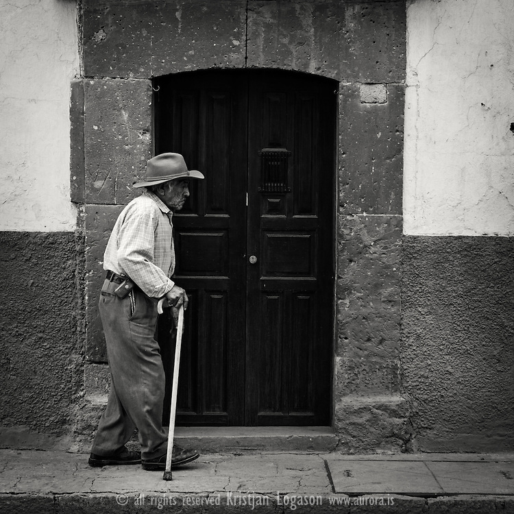 Old man with a walking stick walking in the street of san miguel de