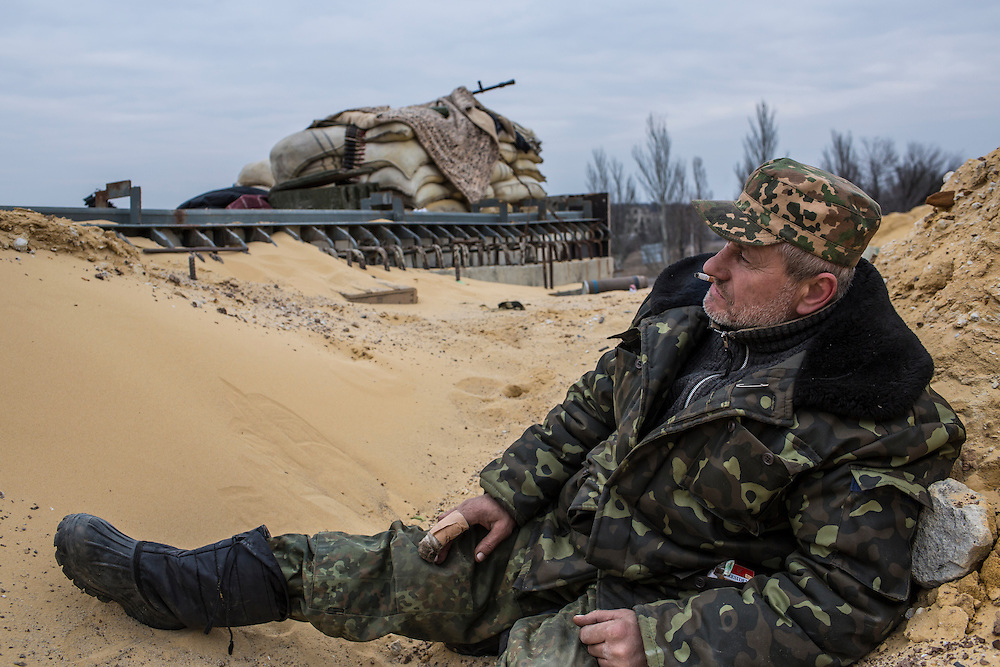 PERVOMAISKE, UKRAINE - MARCH 19, 2015: A fighter who uses the name Uncle Vova, a member of the pro-Ukrainian Dnipro-1 battalion, takes cover behind a berm at one of the group's bases known as The Bridge near ongoing battles for the town of Pisky in Pervomaiske, Ukraine. CREDIT: Brendan Hoffman for The New York Times