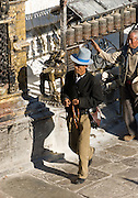 """A man with prayer beads and a tall blue hat walks clockwise around Buddhist Swayambhunath, the """"Monkey Temple"""", Nepal, Asia. Swayambhunath, founded about 500 AD, is one of the oldest and holiest Buddhist sites in the Kathmandu Valley. It sits on a hill in the west of Kathmandu overlooking the city."""