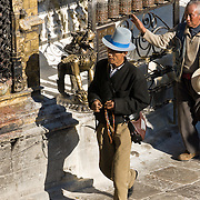 "A man with prayer beads and a tall blue hat walks clockwise around Buddhist Swayambhunath, the ""Monkey Temple"", Nepal, Asia. Swayambhunath, founded about 500 AD, is one of the oldest and holiest Buddhist sites in the Kathmandu Valley. It sits on a hill in the west of Kathmandu overlooking the city."
