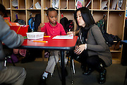 Michelle Rhee speaks with six-year-old Dazhon Turner while touring PS7 in Sacramento, Calif., February 4, 2011.