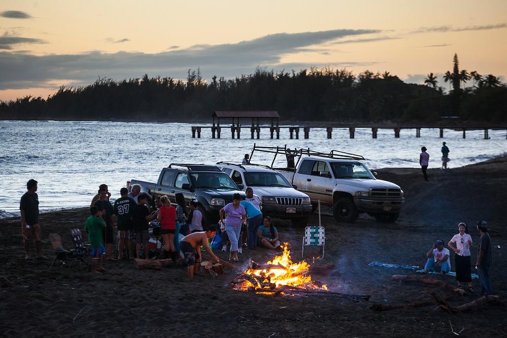 Locals gather for a bonfire and tailgate party on the beach in Waimea, Kauai, Hawaii.