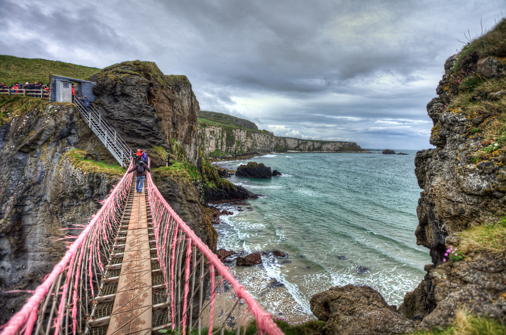 """Carrick-a-Rede Rope Bridge is a famous rope bridge near Ballintoy in County Antrim, Northern Ireland. The bridge links the mainland to the tiny island of Carrickarede (from Irish: Carraig a' Ráid, meaning """"rock of the casting""""). It spans 20 metres (66 ft) and is 30 metres (98 ft) above the rocks below. The bridge is mainly a tourist attraction and is owned and maintained by the National Trust. In 2009 it had 247,000 visitors. The bridge is open all year round (subject to weather) and people may cross it for a fee."""