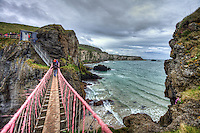 "Carrick-a-Rede Rope Bridge is a famous rope bridge near Ballintoy in County Antrim, Northern Ireland. The bridge links the mainland to the tiny island of Carrickarede (from Irish: Carraig a' Ráid, meaning ""rock of the casting""). It spans 20 metres (66 ft) and is 30 metres (98 ft) above the rocks below. The bridge is mainly a tourist attraction and is owned and maintained by the National Trust. In 2009 it had 247,000 visitors. The bridge is open all year round (subject to weather) and people may cross it for a fee."