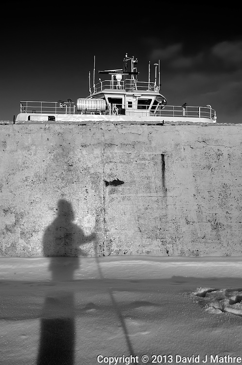 Shadow photographer fishing in Tromsø, Norway. Image taken with a Leica X2 camera (ISO 100, 24 mm, f/5.6, 1/500 sec). Raw image processed with Capture One Pro (including conversion to B&W).