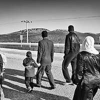Syrian refugees look towards Syria as they walk outside of a refugee camp in Reyhanli, Turkey, Saturday, March 17, 2012. The number of Syrian refugees in Turkey is now about 17,000. March 2012.