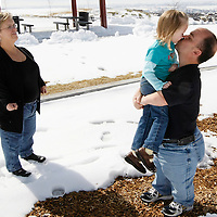 Chris Kotzian (R) kisses daughter Avery, 4 as wife Barb looks on in a park near their home in Thornton, Colorado March 25, 2010.  Chris and Barb are achondroplasia dwarfs while Avery, 4 is average sized. Preferring to be called little persons Chris is active in the Little People of America, the only dwarfism support organization that includes all 200+ forms of dwarfism.  REUTERS/Rick Wilking (UNITED STATES)