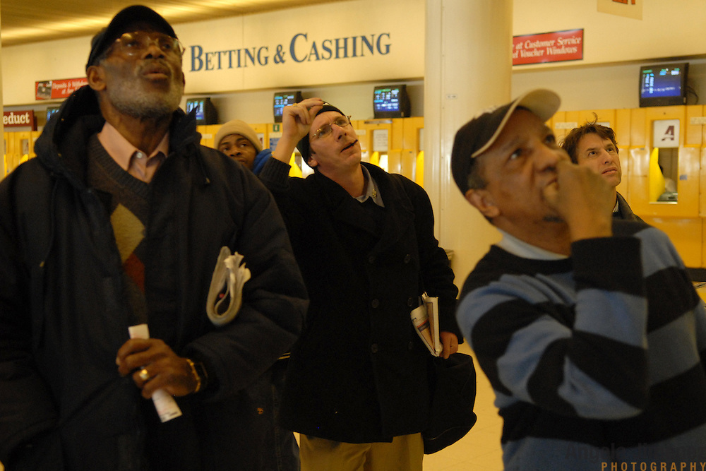 Chuck Drakos, third from right, of Long Island, snaps at his horse as he watches it run on the television at the Aqueduct race track in New York City on February 19, 2007. Drakos, who started coming to the track with his father when he was a boy and comes every day, works out his own elaborate handicaps for all the Aqueduct races every day. He says he wants to get a job as the newspaper handicapper for the New York Post. On this day, he won over $300 on the Pick 4. ..Betting on the horses is still a popular game and the money still flows, but off track betting and other forms of entertainment have eroded live attendance at the races.  The daily diehard betters and horse lovers who sparsely populate the place on work days are joined by a bigger crowd on the weekends. ..The Aqueduct, located in Ozone Park, Queens, is the only horse racing track in New York City and probably the coldest in the country (most of the others are in Kentucky, Florida or California). Horses race on the winterized inner dirt rack from January 1st through the end of April. Aqueduct was built in 1894, renovated in 1959, then opened for winter racing in 1975. It is the winter race track operated by the New York Racing Association (NYRA), which also runs Belmont and Saratoga in the warm seasons. Betters at Aqueduct watch and bet on the nine daily live races and all other races around the country via Simulcast. ..
