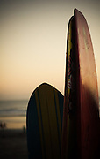 Colourful surfboards stand stand erect as daylight turns to night at Kuta Beach, Bali, Indonesia.