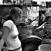 "May 15, 2005 - Managua, Nicaragua - Meiling, 15, a child prostitute (left), and her little sister Aura, wash up outside thier home. Meiling has four siblings and her father left 3 years ago. ""Mother tried to find odd jobs but a friend of mine came to me and told me about working on the highway."".    ""I'm in the 4th grade and I use the money sometimes to buy my notebooks. I go to the afternoon school shift."" .     ""We'd all be starving and i'd rather do what  I do than see my siblings go hungry."""