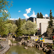 The Whistler on a sunny day in the Spring.  People sit by the Whistler Village water course that runs beside the Maury Young Arts Centre  Whistler BC, Canada.
