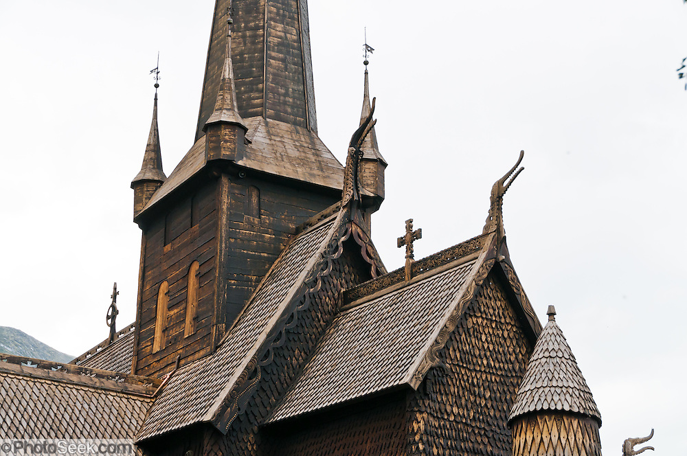 """Turret towers and dragon head design motif. Built in 1170, Lom Stave Church (stavkirke or stavkyrkje) was rebuilt into a cruciform, triple-nave church in 1663 and restored in 1933 and 1973. Visit this wooden Norman-style church in the town of Lom, in Gudbrandsdal, Oppland county, Norway. """"Staves"""" are upright logs that support the central room framework."""