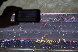 © Licensed to London News Pictures. 23/04/2017. LONDON, UK.  A visitor takes a photograph of runners on Tower Bridge, seen from the glass walkway of Tower Bridge, as runners reach the half way point.  Photo credit: Vickie Flores/LNP