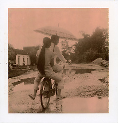 Chocolate Polaroid of two girls riding a bicycle along a puddle filled road on a rainy day, Vietnam, Southeast Asia