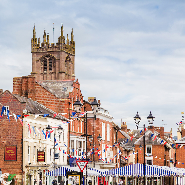 The tower of the historic St. Laurence's Church looms over the Market Square in Ludlow, Shropshire.