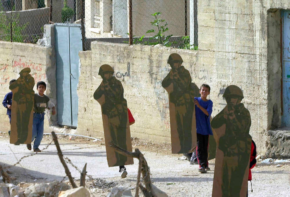 Palestinian boys carry Israeli army firing range targets in the likeness of soldiers, through the streets of the West Bank village of Beit Rima Thursday Oct. 25, 2001 near a home stormed by Israeli soldiers on Wednesday. Israeli troops withdrew early Thursday from the Palestinian village taken a day earlier in which five Palestinians were killed.