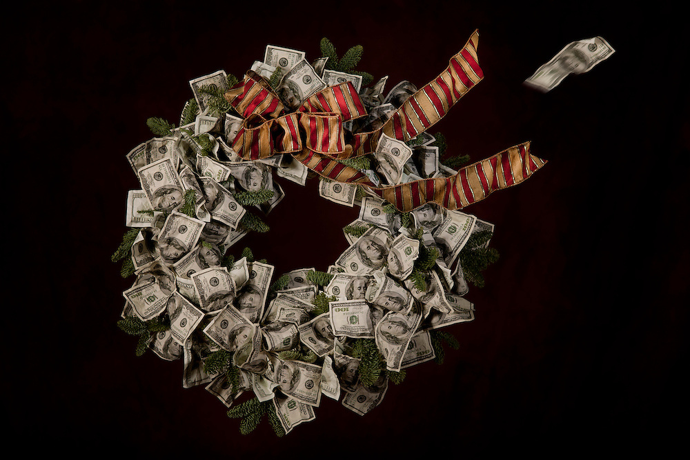 A Wreath-o-Franklins Christmas card. Red and gold bow tops the wreath as the ribbon blows in the wind with a passing one hundred dollar bill.