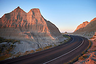 A car drives down the road in Badlands National Park, South Dakota.
