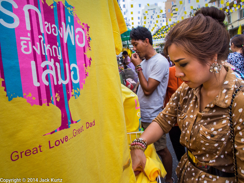 28 NOVEMBER 2014 - BANGKOK, THAILAND:  A woman in Bangkok looks at yellow tee shirts before the King's Birthday in Thailand. Bhumibol Adulyadej, the King of Thailand, was born on December 5, 1927, in Cambridge, Massachusetts. The family was in the United States because his father, Prince Mahidol, was studying Public Health at Harvard University. He has reigned since 1946 and is the world's currently reigning longest serving monarch and the longest serving monarch in Thai history. Bhumibol, who is in poor health, is revered by the Thai people. His birthday is a national holiday and is also celebrated as Father's Day. He is currently hospitalized in Siriraj Hospital, recovering from a series of health setbacks. Thousands of people come to the hospital every day to sign get well cards for the King. People wear yellow at events associated with the King because he was born on a Monday, and yellow is Monday's color in Thai culture. It's also the color of the monarchy.      PHOTO BY JACK KURTZ