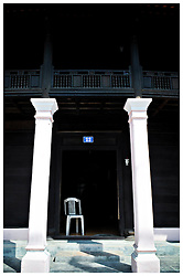 Two white columns frame the doorway of an old colonial style house in Hue, Vietnam, Southeast Asia