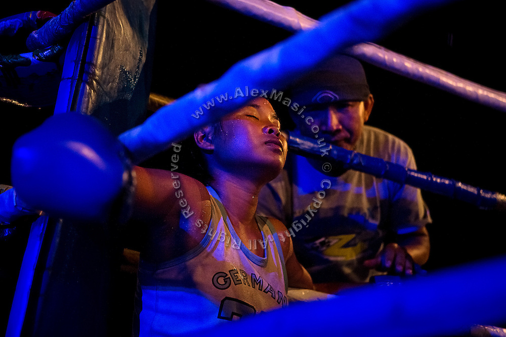 An adolescent girl is relaxing for a second, while sitting at her corner during a break of her Muay Thai boxing match, organised in a village near Ubon Ratchathani, northeast Thailand.