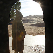 Man in a djallaba, standing in front of the Auberge Du Sud Kasbah Lodge, in Erg Chebbi Dunes, Morocco.