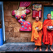Buddhist monks pause to be photographed on Patpong Road outside a popular night club in Bangkok, Thailand.