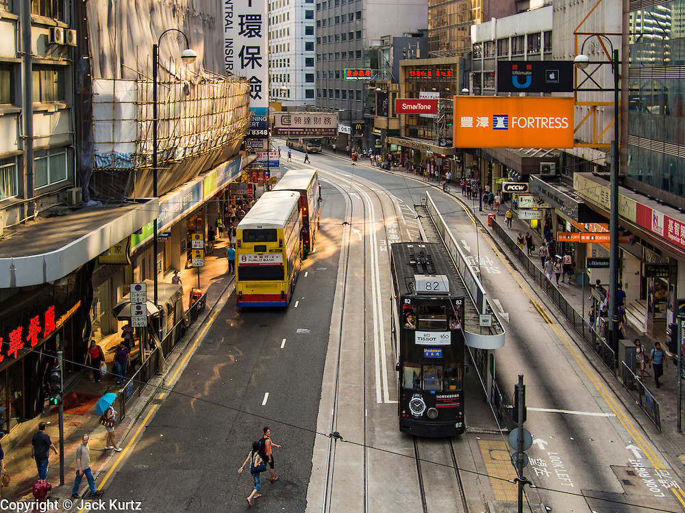 10 AUGUST 2013 - HONG KONG: Trams and busses in the Central Business District of Hong Kong. Hong Kong is one of the two Special Administrative Regions of the People's Republic of China, Macau is the other. It is situated on China's south coast and, enclosed by the Pearl River Delta and South China Sea, it is known for its skyline and deep natural harbour. Hong Kong is one of the most densely populated areas in the world, the  population is 93.6% ethnic Chinese and 6.4% from other groups. The Han Chinese majority originate mainly from the cities of Guangzhou and Taishan in the neighbouring Guangdong province.      PHOTO BY JACK KURTZ