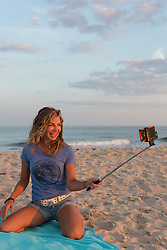 woman at the beach with a selfie stick