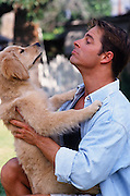 man holding a yellow lab puppy