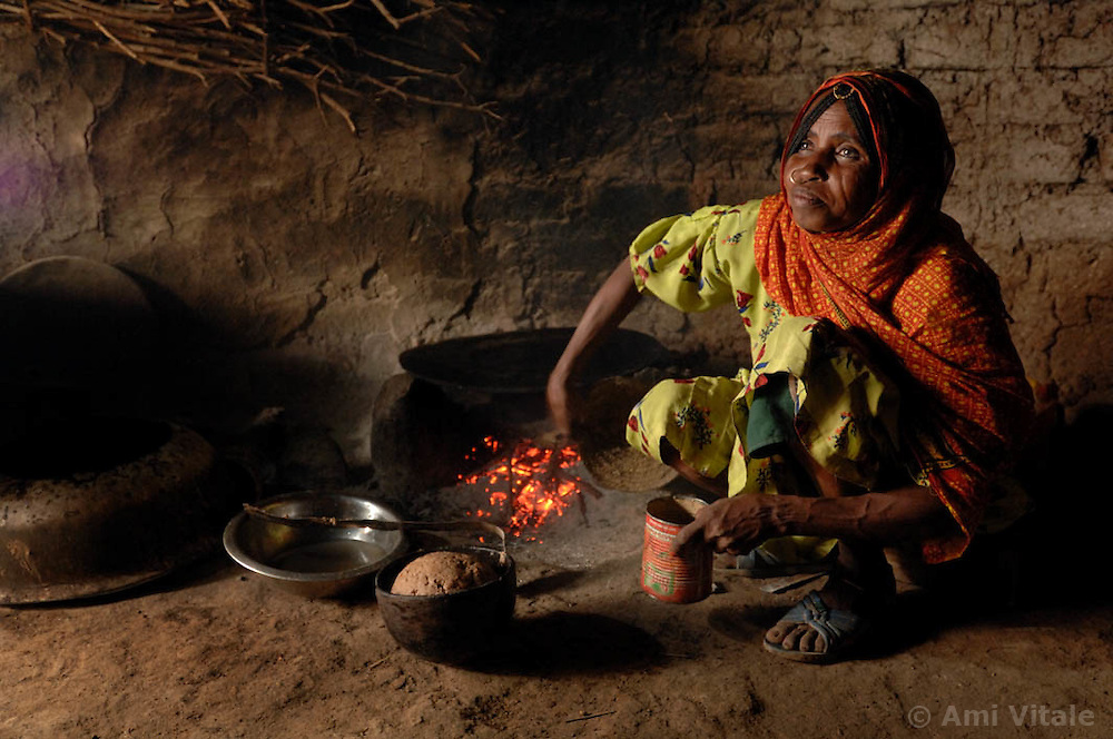 "Kadija makes a traditional bread  called injero, inside her home  in Barentu, Eritrea August 25, 2006. Kadija is a traditional birth assistant as well as a recipient of a donkey from the women's union ""Hamade"". (Ami Vitale)"