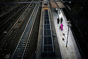 Three Muslim women walking on a train platform. In 2008 about 1 in 17 of the city's population was foreign born. This influx of migrants clearly makes its mark on the city