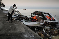 As an other raft comes in, a Greek woman sweeps debris from a wooden boat wreck that brought refugees earlier. All boats are destroyed or disabled for no second use in ferrying asylum seekers. Refugees from Afghanistan and Syria arrive in boats on the shores of Lesbos near Skala Sikaminias, Greece on 06<br /> November, 2015. Lesbos, the Greek vacation island in the Aegean Sea between Turkey and Greece, faces massive refugee flows from the Middle East countries.