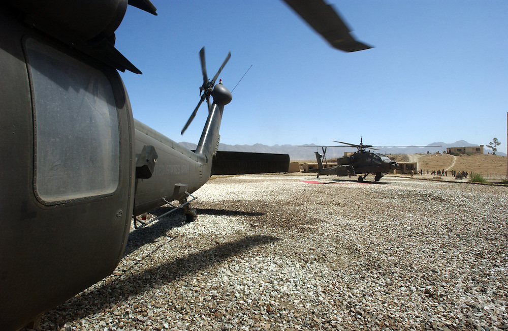 A U.S. Army UH-60 Black Hawk (l) and its' AH-64 Apache helicopter gunship escort make a stop at a base in Kabul, Afghanistan June 17, 2002. Coalition forces continue to scour Afghanistan for traces of remaining al Qaeda and Taliban fighters as part of the ongoing Operation Enduring Freedom.