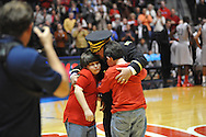"""Col. Chris Davis greets his family Lori and sons Braxton (wearing glasses) and McKinley at the Ole Miss vs. Alabama game at the C.M. """"Tad"""" Smith Coliseum in Oxford, Miss. on Wednesday, February 26, 2014. (AP Photo/Oxford Eagle, Bruce Newman)"""